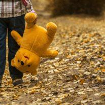 Barn med nallebjörn med föräldrar som flyttar isär
